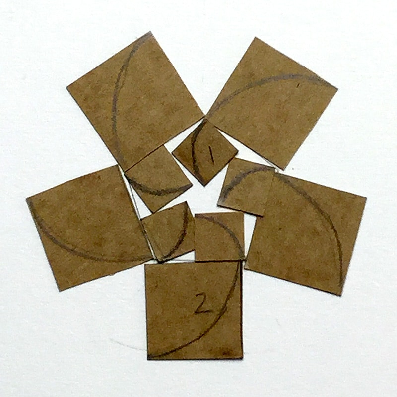 brown paper cut into squares and arranged in a pentagram