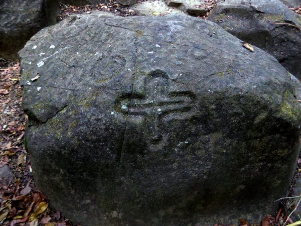 petroglyph of an equal armed cross on a rock, a light spiral can be seen faintly as well