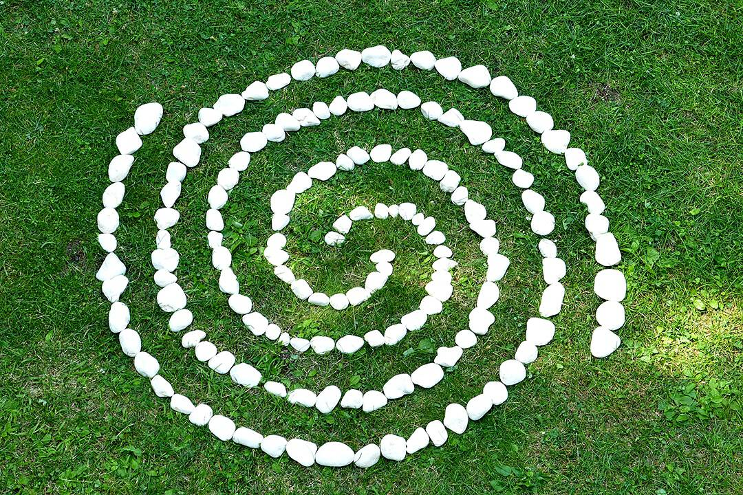 double spiral make with white rocks places on green grass