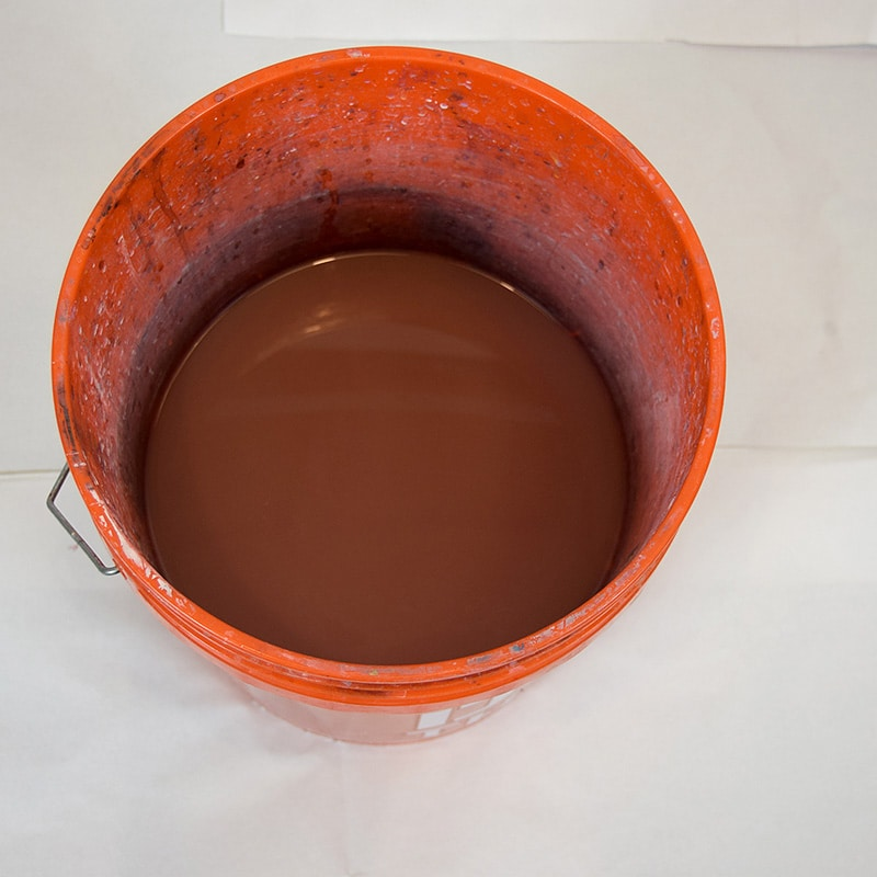 a five gallon bucket approximately half full of water that was used to clean paint brushes
